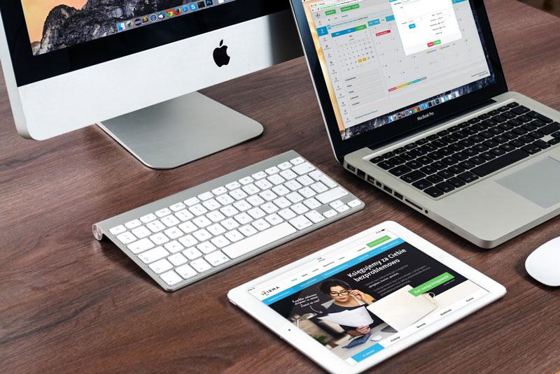 desktop, notebook, table e teclado Apple dispostos sobre a mesa