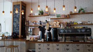 Interior de uma cafeteria charmosa, com os utensílios e maquinário expostos em cima do balcão